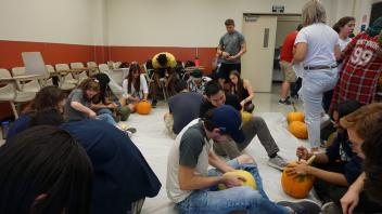 Members carving pumpkins