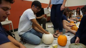 Joseph Quesada scooping the insides of a pumpkin!